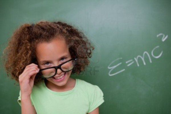 11679644-smart-schoolgirl-looking-above-her-glasses-in-front-of-a-blackboard